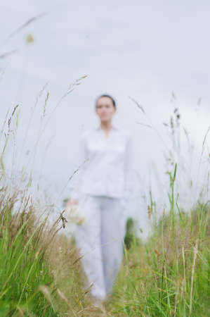 The woman in white clothes with a bouquet in her hand in the field of grass Фото со стока