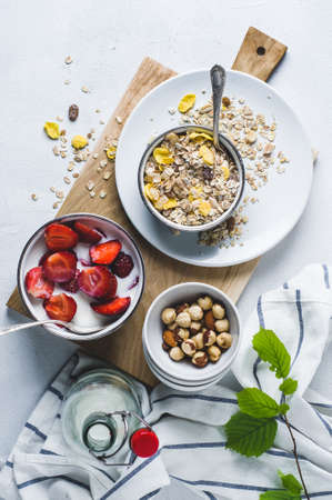 Muesli with fresh strawberries in a plate over a white concrete background