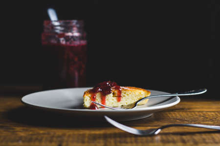 Portion of homemade pie with strawberry jam in a grey ceramic plate
