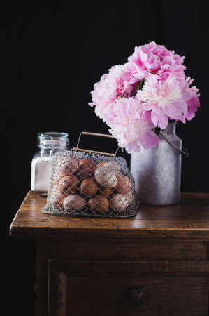 Concept of rural kitchen. Peonies in a can, flour and eggs on a wooden table against the background of a black wall