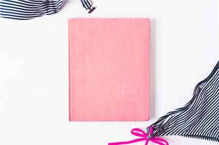 Retro style striped swimsuit and pink book cover on a white concrete background