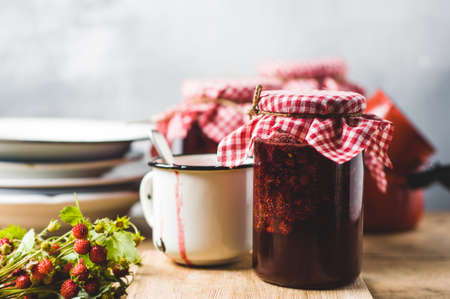 Homemade strawberry jam in jars and inredients on a wooden cutting board Stock Photo