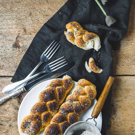 Homemade buns with poppy seeds on a white plate over old wooden table Imagens