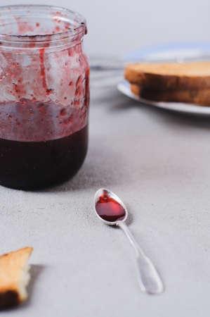 Eigengemaakte aardbeijam in kruik en snacks op een grijze concrete achtergrond Stockfoto - 83873266
