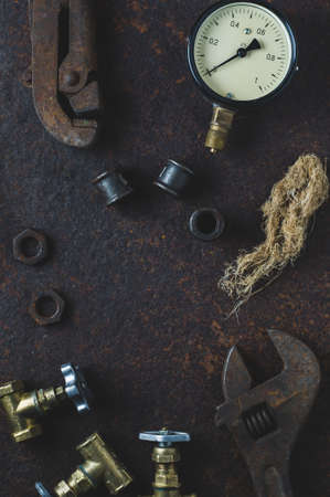 Old wrenches and water gates on a rusty iron background 版權商用圖片