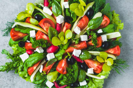 Fresh lettuce, tomatoes, olives and feta cheese in a bowl