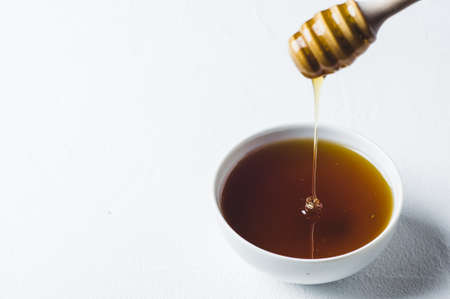 Fresh honey in a white cup on a white concrete background Banco de Imagens