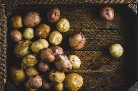 Fresh potatoes in an old wooden box Banco de Imagens - 84394077
