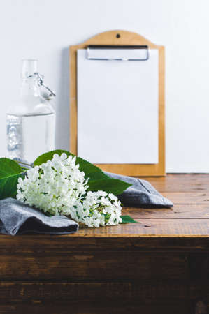 A bottle of water and a hydrangea flower on old wooden table