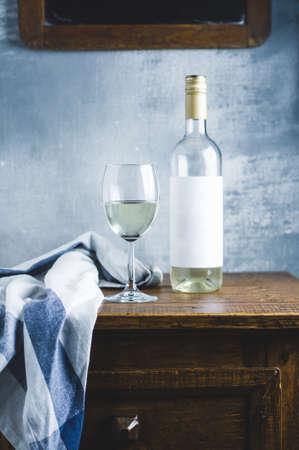 화이트 와인 한 잔과 오래된 나무 테이블에 병 유리
