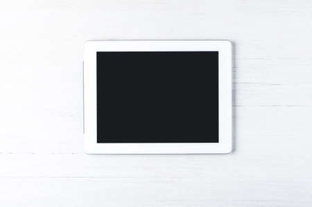 白い木製のテーブル上のタブレット コンピューター。コピーのテキストやデザインのための領域