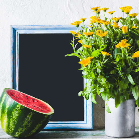 Still life with yellow flowers and watermelon