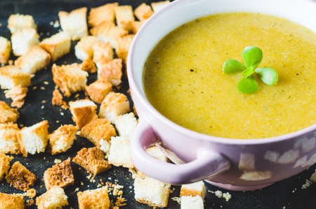 Vegetable cream soup in a pink bowl and croutons on a dark background Фото со стока - 83875681