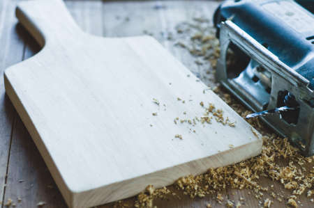 Jigsaws and shavings on wooden background. Woodworking or carpentry concept