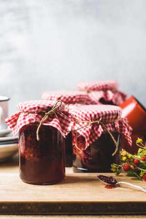 Zelfgemaakte Aardbeienjam in potten en ingrediënten op een houten snijplank
