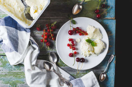 Homemade ice cream with red currants and berries on a plate over old wooden table Stock Photo