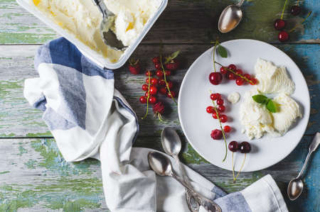 Homemade ice cream with red currants and berries on a plate over old wooden table Stok Fotoğraf