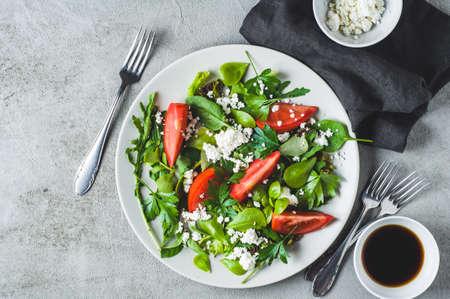 회색 세라믹 접시에 신선한 토마토 샐러드. 다이어트 또는 깨끗한 먹는 개념