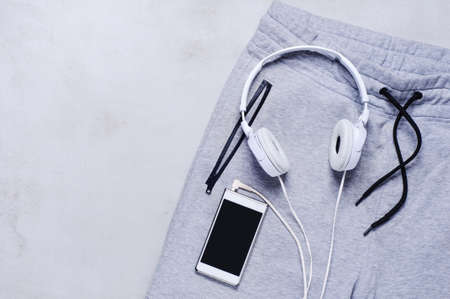 Sportswear, headphones and smartphone on the grey background. The concept of sport or exercise