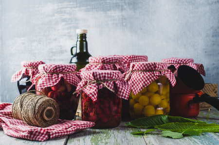Homemade canned vegetables and fruits in glass jars on a wooden table Banco de Imagens - 84743984