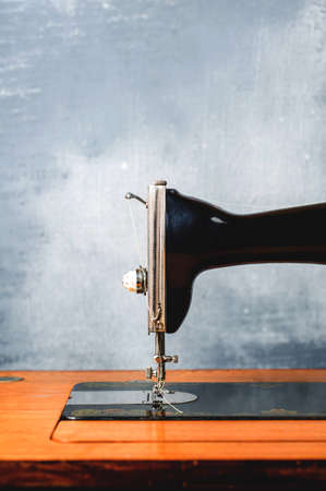 Old vintage sewing machine on a gray background