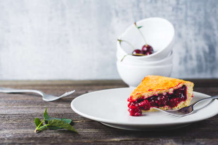 Cherry pie and fresh berries in a bowl on a dark wooden table
