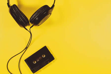Headphones old audio cassette tape on a yellow background
