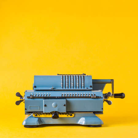 Old calculating machine on yellow background. Accounting or business concept