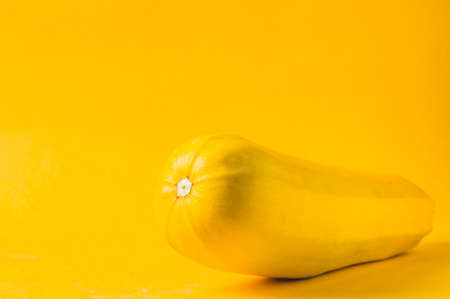 Yellow squash on a yellow background. Negative space for text
