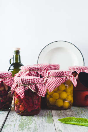 Homemade canned vegetables and fruits in glass jars on a wooden table Banco de Imagens - 85167922
