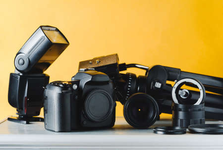 黄色の背景に写真家のデジタルカメラ、レンズと機器