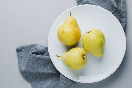 Ripe yellow pear on a white ceramic plate