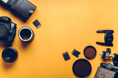 디지털 카메라, 렌즈 및 노란색 배경에 사진 작가의 장비 스톡 콘텐츠