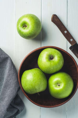 Green apples in a bowl on a light wooden background. Diet or healthy eating concept Banco de Imagens