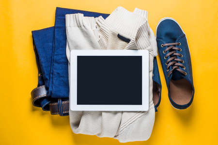 Fashionable mens clothing. Jeans and shoes on yellow background