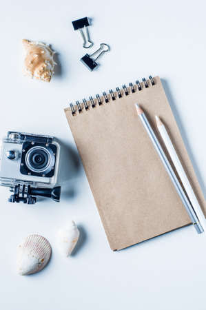 subsea: Action camera, shells and notebooks on a light background. The concept of memories or dreams Stock Photo