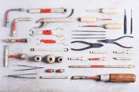 A set of old tools for the professional mechanic over gray concrete background
