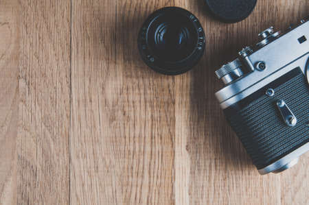 Old camera and lens on wooden table. The view from the top. Space for text or design