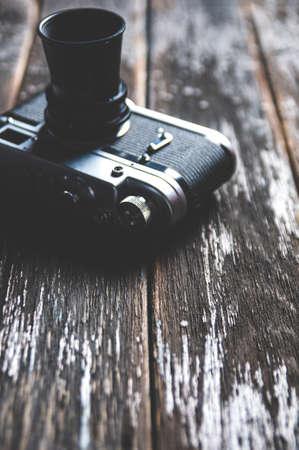 Old camera on dark wooden background Imagens