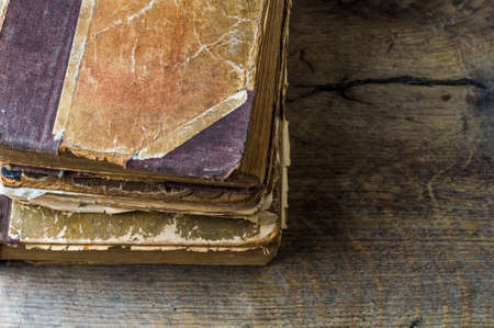 Old tattered book on wooden background