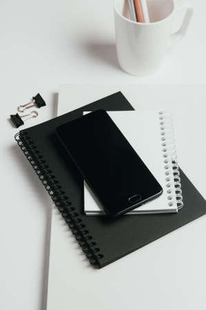 Black smartphone and notebooks on light background. Top view Standard-Bild - 121677307