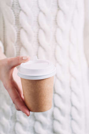 A woman in a white sweater holding a paper Cup of coffee. Template for text or design Standard-Bild - 121677382