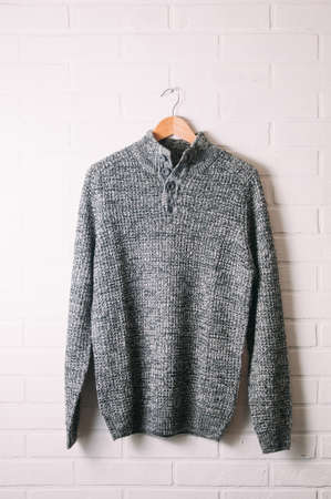 Mens winter sweater on brick wall background