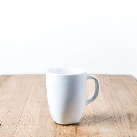 White mug on a wooden table. Template for text or design Standard-Bild - 121677490