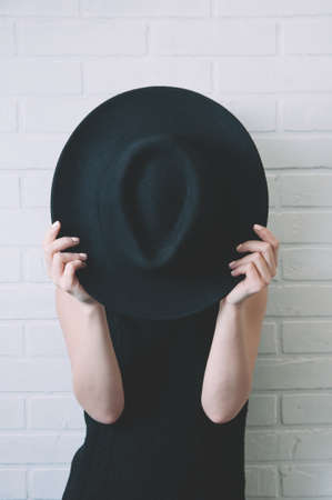 A woman on a white wall hides her face behind a big black hat Banco de Imagens
