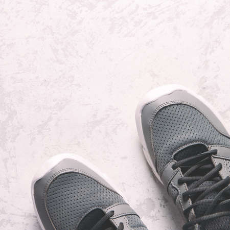Grey sneakers on grey background. Sport or street concept