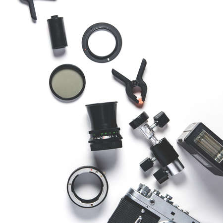 Old camera and photo accessories on white background