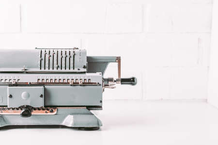 Old calculating machine on white background. Accounting or business concept Standard-Bild - 121678315
