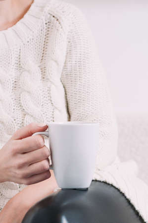 A woman in a white sweater holding a white mug in her hands. Template for text or design Standard-Bild - 121678355