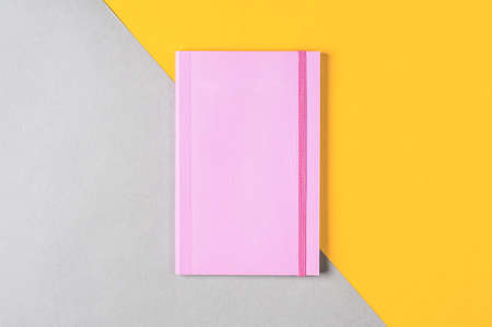 Pink notepad on grey-yellow background Standard-Bild - 121678442